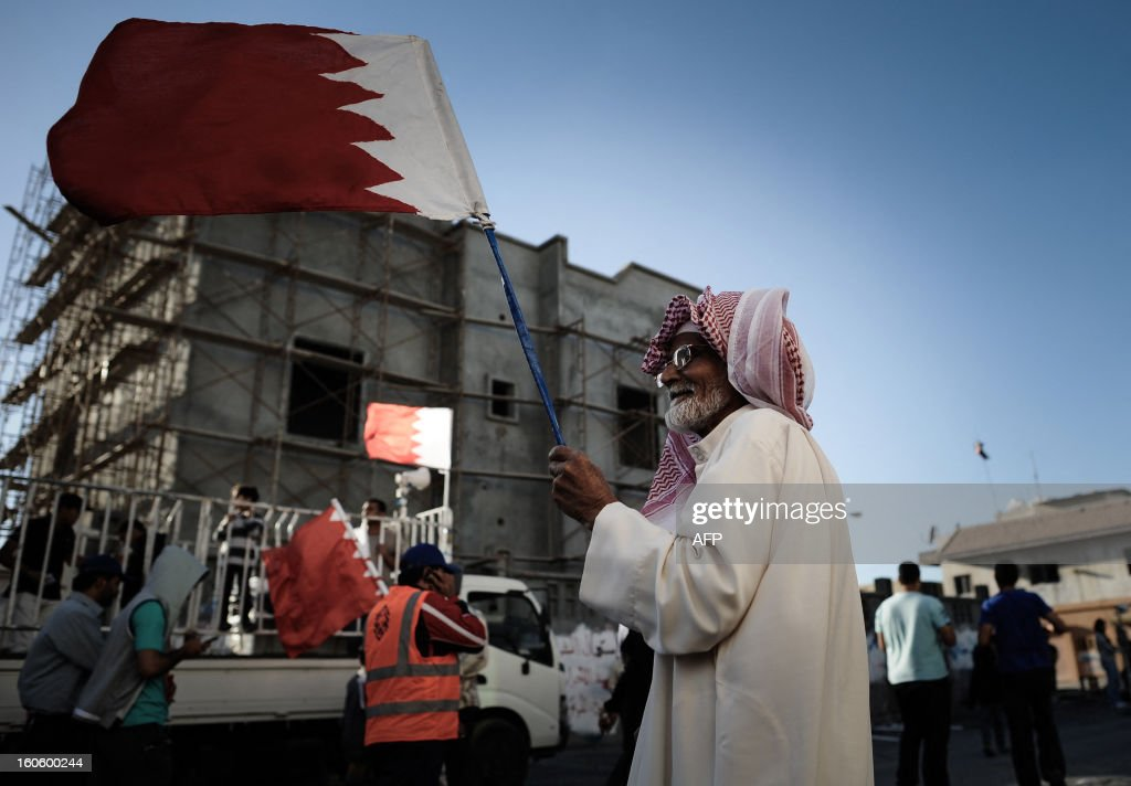 A Bahraini Shiite Muslim man waves his national flag as he takes part in an anti-government rally to demand reforms in the village of Malikiya, South of Manama, on February 3, 2013. The Gulf state has been shaken by unrest since its forces in March 2011 crushed a month of popular Shiite-led protests demanding greater rights and an end to what they said was discrimination by the Sunni royals. AFP PHOTO/MOHAMMED AL-SHAIKH