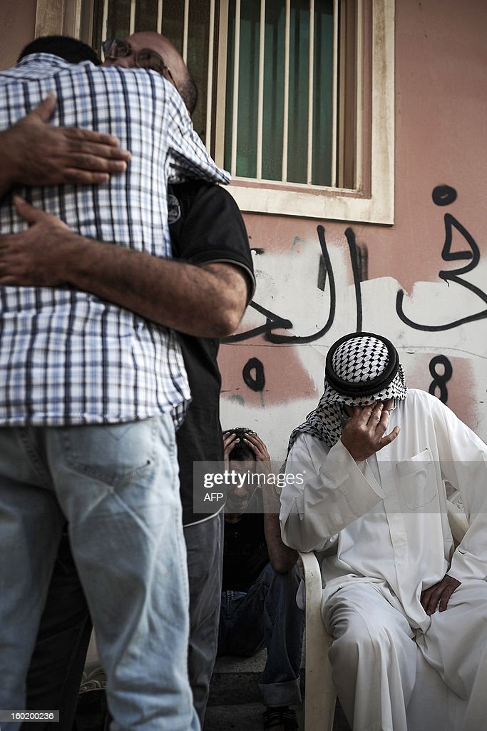 Bahraini Shiite Muslim men mourn during the funeral of an a eight-year-old child on January 27, 2013 in the village of Daih, west of Manama. The child, Qassim Habib Marzooq, died at hospital after developing respiratory complications and his relatives claim that his death is due to the inhalation of poisonous tear gas that riot police used during a protest in January 2013. AFP PHOTO/MOHAMMED AL-SHAIKH
