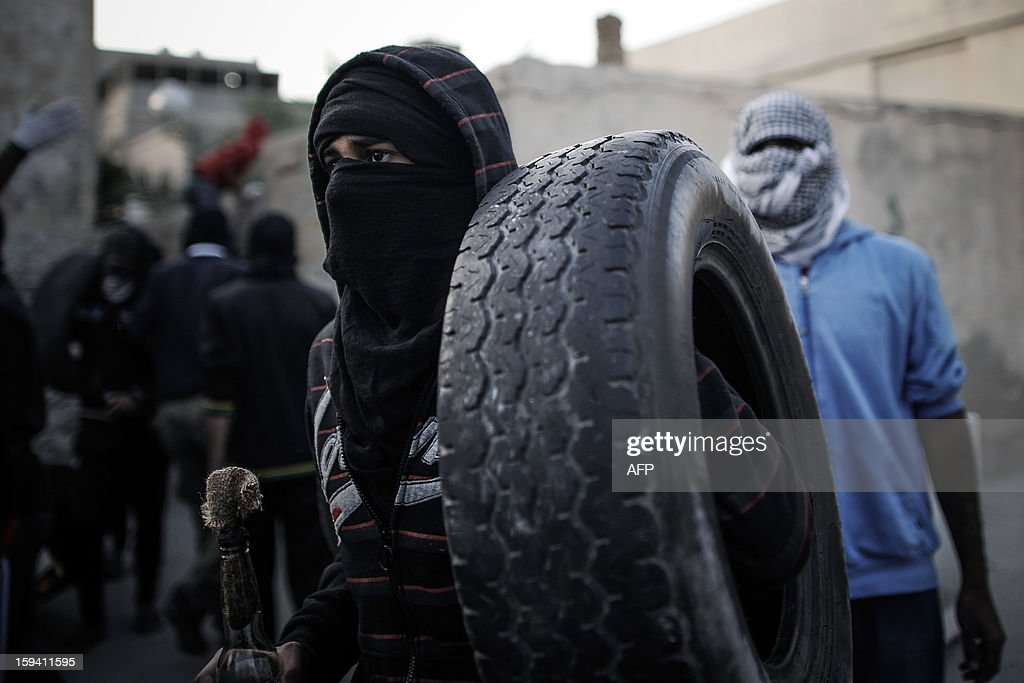 Bahraini Shiite Muslim protestor carries a tyre and a petrol bomb during clashes with riot police following the funeral of Habib Ebrahim Abdullah on January 13, 2013 in the village of Malikiyah, south of Manama. Abdullah, 88, died at hospital after developing respiratory complications and his relatives claim that his death is due to the inhalation of poisonous tear gas that riot police used during a protest in October 2012.