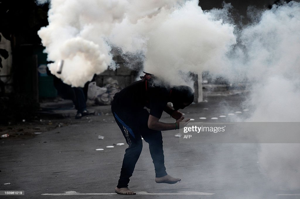 A Bahraini Shiite Muslim protestor ducks as a tear gas canister fired by riot policemen flies overhead, during clashes following the funeral of 16-year-old Ali Abbas Radhi in the village of Samahij, Muharraq City, east of capital Manama on November 10, 2012. The Shiite Muslim teenager died after he was knocked down by a car while being chased by Bahraini police during a crackdown on protesters, the opposition said. AFP PHOTO/MOHAMMED AL-SHAIKH