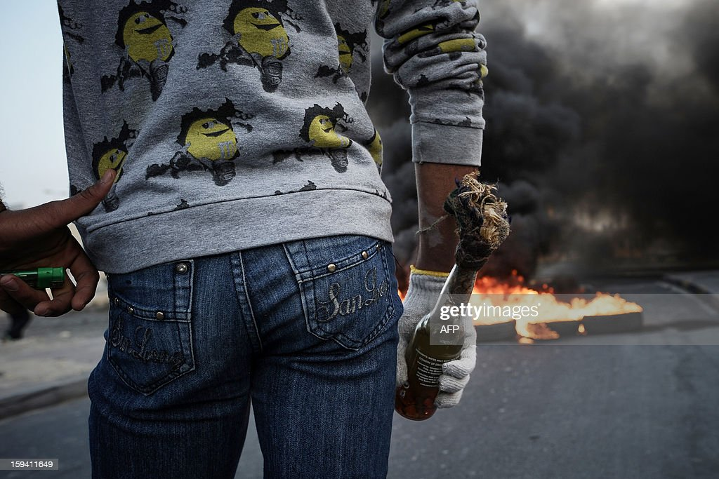 Bahraini Shiite Muslim protestor holds a petrol bomb during clashes with riot police following the funeral of Habib Ebrahim Abdullah on January 13, 2013 in the village of Malikiyah, south of Manama. Abdullah, 88, died at hospital after developing respiratory complications and his relatives claim that his death is due to the inhalation of poisonous tear gas that riot police used during a protest in October 2012.