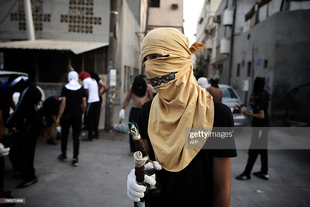 A Bahraini Shiite Muslim protestor holds petrol bombs to be used against riot police during an anti-government demonstration on the third day after the funeral of 16-year-old Ali Abbas Radhi in the village of Samahij, east of the capital Manama, on November 13, 2012. The Shiite teenager died on November 9, after he was knocked down by a car while being chased by Bahraini police during a crackdown on protesters, the opposition said. AFP PHOTO/MOHAMMED AL-SHAIKH