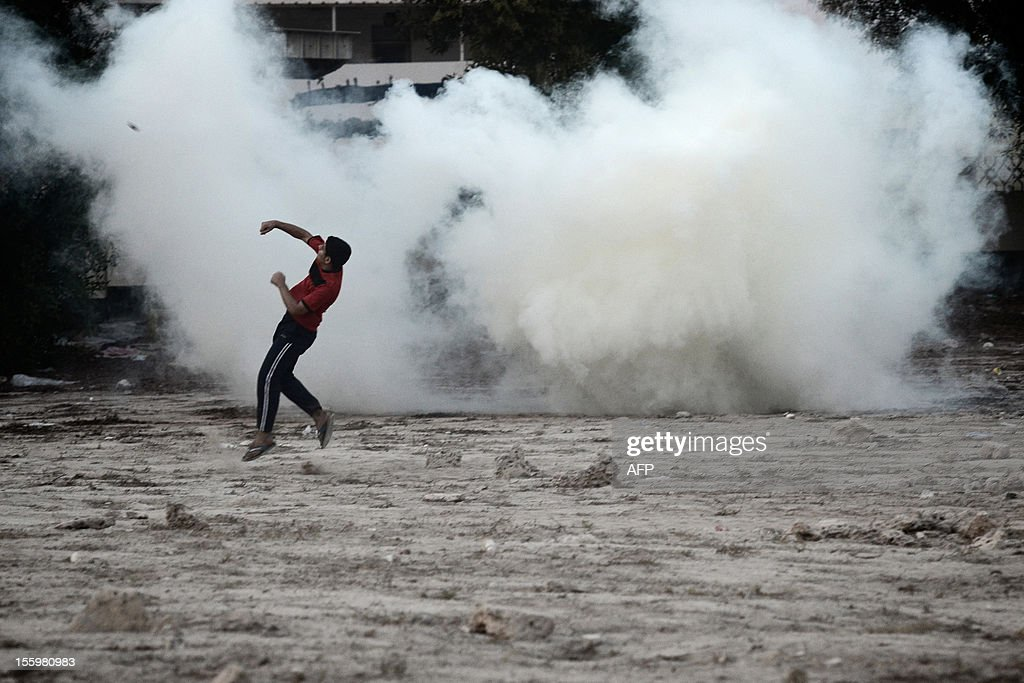 A Bahraini Shiite Muslim protestor is seen as tear gas is fired by riot policemen during clashes following the funeral of 16-year-old Ali Abbas Radhi in the village of Samahij, Muharraq City, east of capital Manama on November 10, 2012. The Shiite Muslim teenager died after he was knocked down by a car while being chased by Bahraini police during a crackdown on protesters, the opposition said.