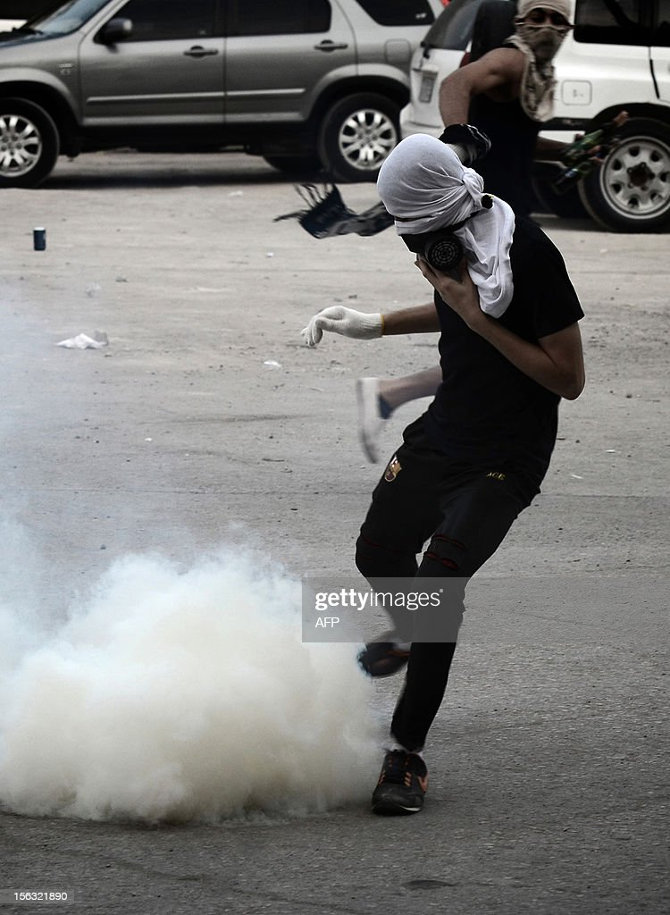 A Bahraini Shiite Muslim protestor runs away from a tear gas fired by riot police during an anti-government demonstration on the third day after the funeral of 16-year-old Ali Abbas Radhi in the village of Samahij, east of the capital Manama, on November 13, 2012. The Shiite teenager died on November 9, after he was knocked down by a car while being chased by Bahraini police during a crackdown on protesters, the opposition said.
