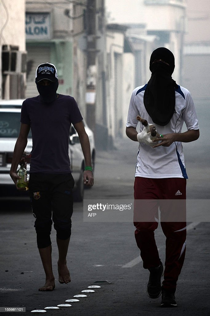 Bahraini Shiite Muslim protestors prepare to throw a petrol bomb at riot police during clashes following the funeral of 16-year-old Ali Abbas Radhi in the village of Samahij, Muharraq City, east of capital Manama on November 10, 2012. The Shiite Muslim teenager died after he was knocked down by a car while being chased by Bahraini police during a crackdown on protesters, the opposition said.