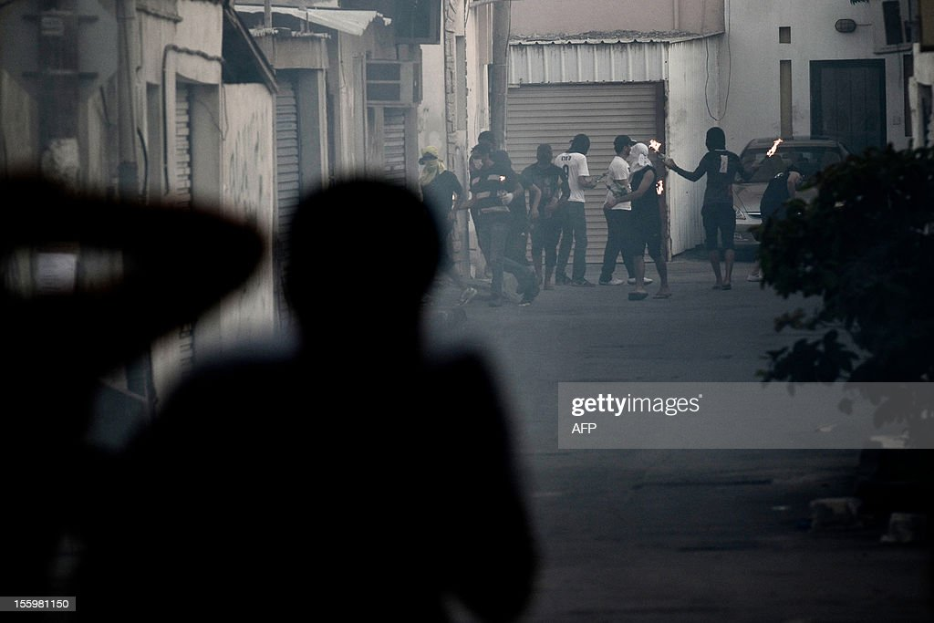 Bahraini Shiite Muslim protestors prepare to throw a petrol bomb at riot police who responded by firing bird shots and tear gas during clashes following the funeral of 16-year-old Ali Abbas Radhi in the village of Samahij, Muharraq City, east of capital Manama on November 10, 2012. The Shiite Muslim teenager died after he was knocked down by a car while being chased by Bahraini police during a crackdown on protesters, the opposition said. AFP PHOTO/MOHAMMED AL-SHAIKH