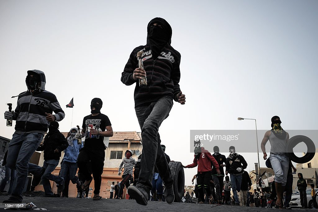 Bahraini Shiite Muslim protestors run towards riot police holding petrol bombs during clashes following the funeral of Habib Ebrahim Abdullah on January 13, 2013 in the village of Malikiyah, south of Manama. Abdullah, 88, died at hospital after developing respiratory complications and his relatives claim that his death is due to the inhalation of poisonous tear gas that riot police used during a protest in October 2012.