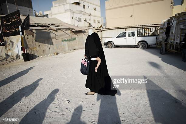A Bahraini Shiite Muslim woman carries her child during a ceremony marking Ashura which commemorates the seventh century slaying of Imam Hussein the...