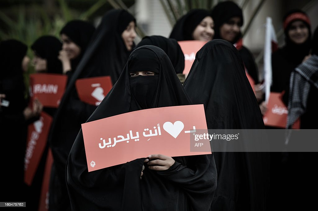 A Bahraini Shiite Muslim woman holds a sign reading 'You are in my heart, Bahrain' as she takes part in an anti-government protest in the village of South Sehla, south of Manama, on February 1, 2013. The Gulf state has been shaken by unrest since its forces in March 2011 crushed a month of popular Shiite-led protests demanding greater rights and an end to what they said was discrimination by the Sunni royals. AFP PHOTO/MOHAMMED AL-SHAIKH