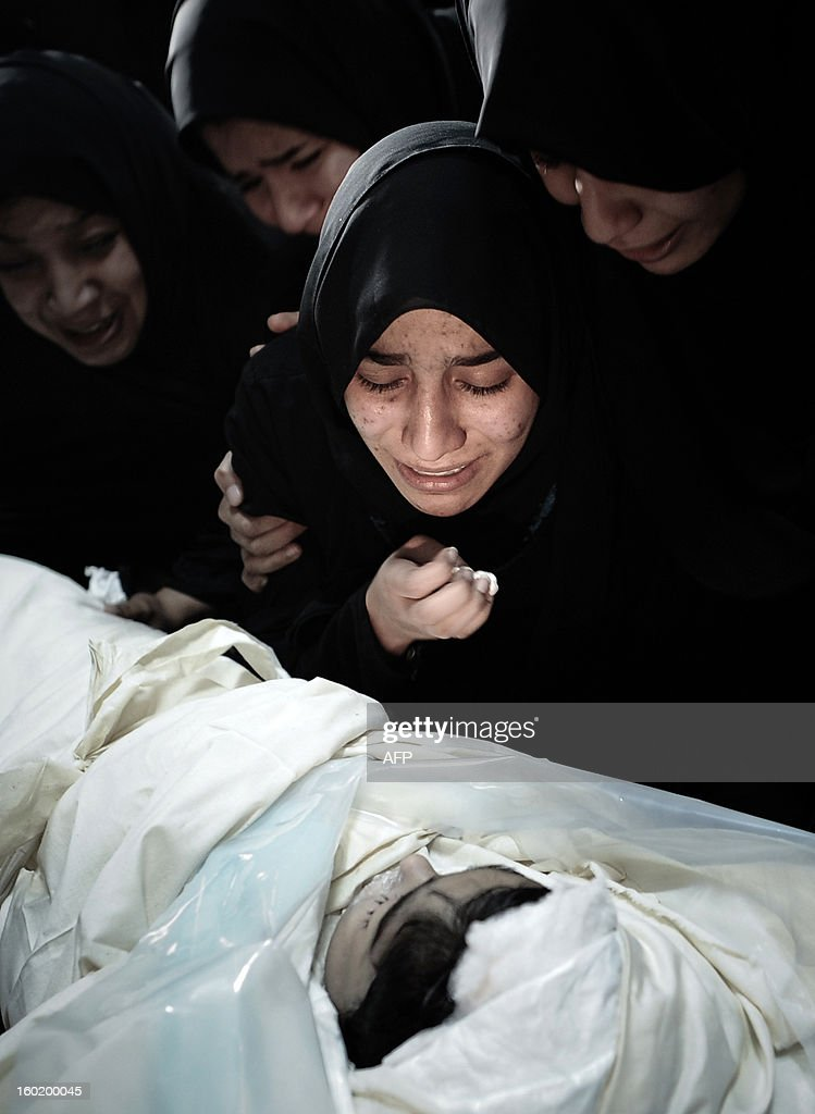 A Bahraini Shiite Muslim woman mourns in front of the corpse of an a eight-year-old child, during his funeral on January 27, 2013 in the village of Daih, west of Manama. The child, Qassim Habib Marzooq, died at hospital after developing respiratory complications and his relatives claim that his death is due to the inhalation of poisonous tear gas that riot police used during a protest in January 2013.