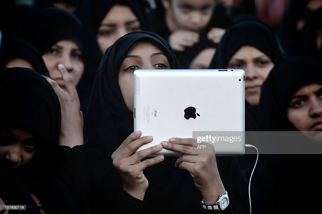 A Bahraini Shiite Muslim woman takes pictures with her iPad during an anti-government rally in the village of Muqsha, west of Manama on December 7, 2012.