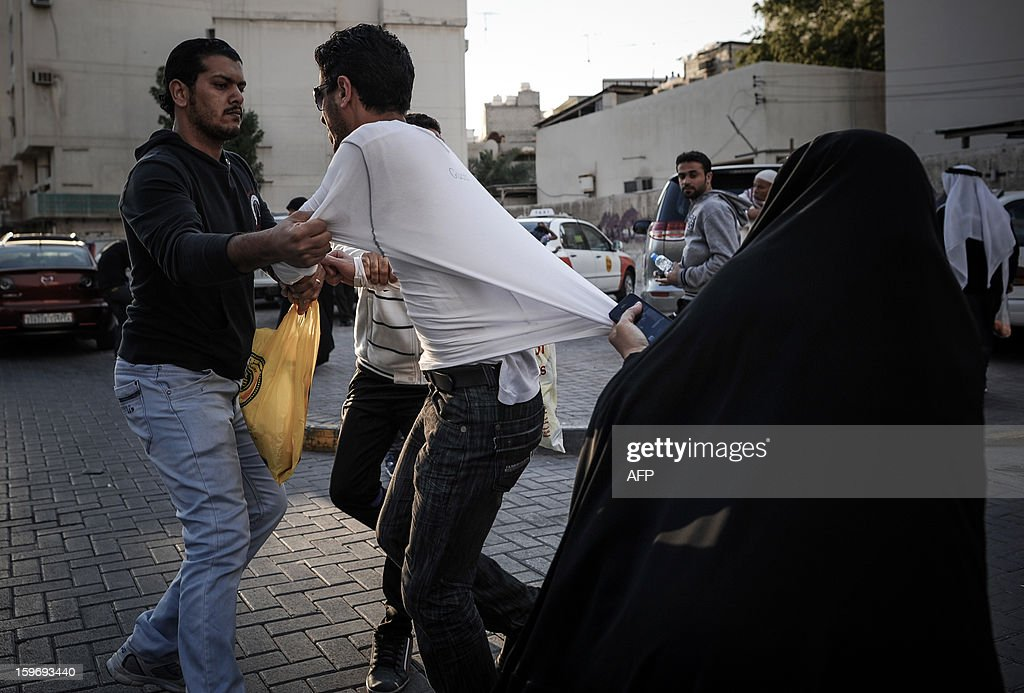 A Bahraini shiite Muslim woman (R) tries to stop one of the protestors (C) after he was arrested by riot police (L) during a demonstration called for by the February 14 Youth Coalition, an Internet group that regularly calls for protests in the Shiite-majority kingdom on January 18, 2013 in the capital Manama. Bahrain's government said the demonstration had not been authorised and warned security forces would prevent it from going ahead.
