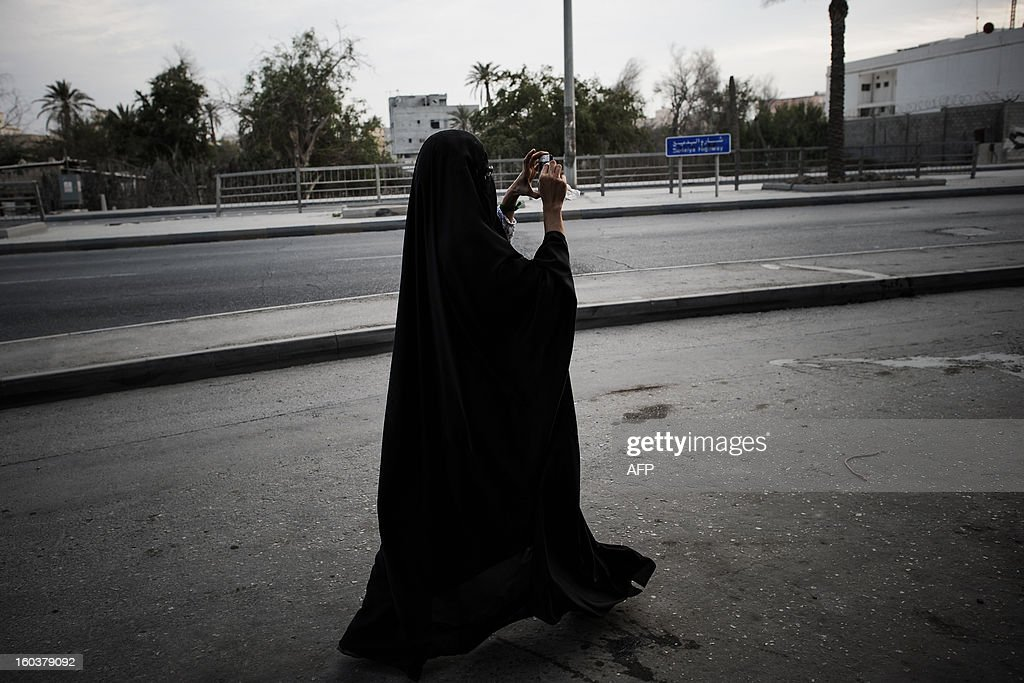 A Bahraini Shiite Muslim woman uses her phone to take pictures of clashes between anti-regime protesters and riot police in the village of Daih, west of Manama, on January 30, 2013 following a demonstration against the death of a child. The child, Qassim Habib Marzooq, died in hospital after developing respiratory complications and his relatives claim that his death is due to the inhalation of poisonous tear gas that riot police used during a protest in January 2013.