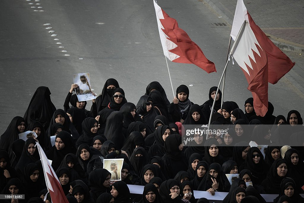 Bahraini Shiite Muslim women hold national flags as they take part in the funeral of Habib Ebrahim Abdullah on January 13, 2013 in the village of Malikiyah, south of Manama. Abdullah, 88, died at hospital after developing respiratory complications and his relatives claim that his death is due to the inhalation of poisonous tear gas that riot police used during a protest in October 2012.