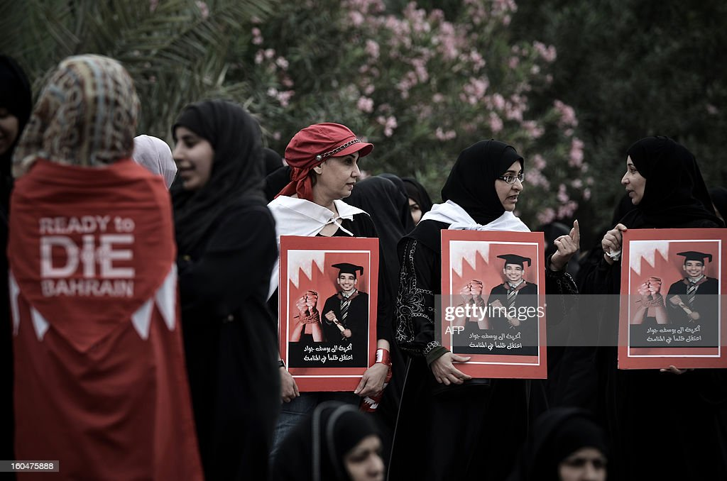 Bahraini Shiite Muslim women hold pictures of a prisoner reading 'Freedom to Yussef Jawad unjustly arrested in Manama' during an anti-government demonstration in the village of South Sehla, south of Manama, on February 1, 2013. The Gulf state has been shaken by unrest since its forces in March 2011 crushed a month of popular Shiite-led protests demanding greater rights and an end to what they said was discrimination by the Sunni royals. AFP PHOTO/MOHAMMED AL-SHAIKH