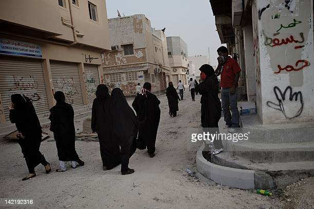 Bahraini Shiite Muslim women protest in the street next a wall reading in Arabic 'down with the Hamad' refering to the Bahraini King Hamad bin Issa...