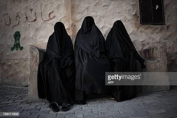 Bahraini Shiite Muslim women sit during the funeral of Habib Ebrahim Abdullah on January 13 2013 in the village of Malikiyah south of Manama Abdullah...