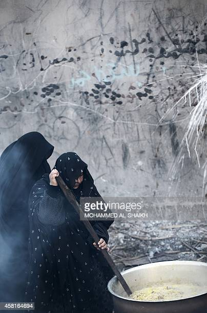 Bahraini Shiite Muslim women stir a pot of rice meat and vegetables being prepared to feed participants in a ceremony marking Ashura which...