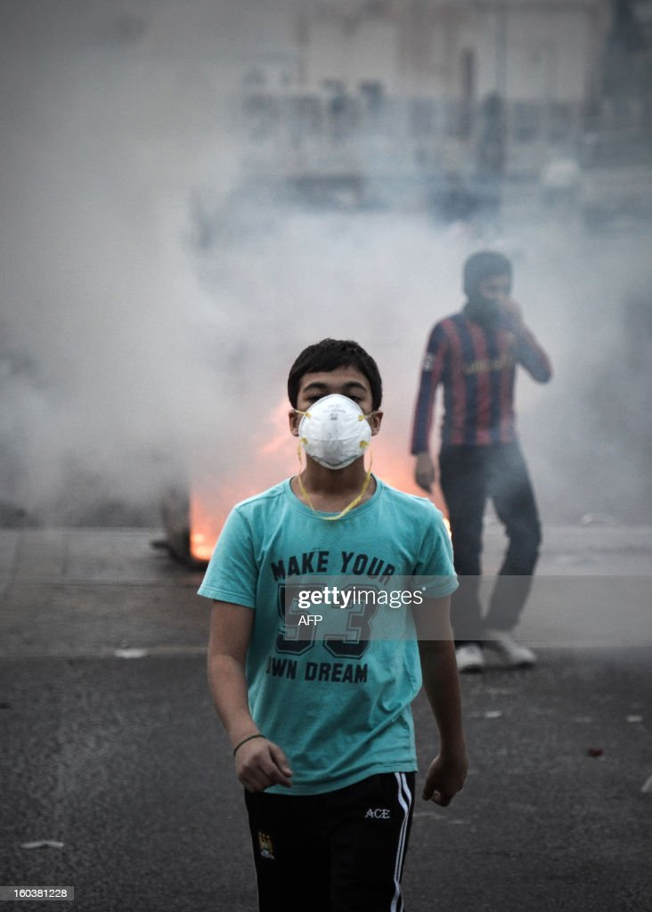 A Bahraini Shiite Muslim youth wearing a mask to protect himself from tear gas walks past a burning garbage container set on fire during clashes with riot police following an anti-government demonstration against the death of a child, in the village of Daih, west of Manama, on January 30, 2013. The child, Qassim Habib Marzooq, died in hospital after developing respiratory complications and his relatives claim that his death is due to the inhalation of poisonous tear gas that riot police used during a protest in January 2013. AFP PHOTO/MOHAMMED AL-SHAIKH