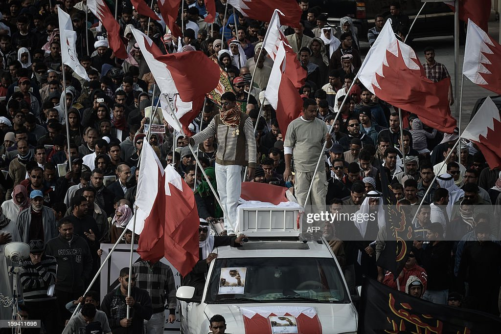 Bahraini Shiite Muslims hold national flags on the top of a van during the funeral of Habib Ebrahim Abdullah on January 13, 2013 in the village of Malikiyah, south of Manama. Abdullah, 88, died at hospital after developing respiratory complications and his relatives claim that his death is due to the inhalation of poisonous tear gas that riot police used during a protest in October 2012. AFP PHOTO/MOHAMMED AL-SHAIKH