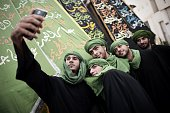 Bahraini Shiite Muslims pose for a selfie during a ceremony marking Ashura which commemorates the seventh century slaying of Imam Hussein the...
