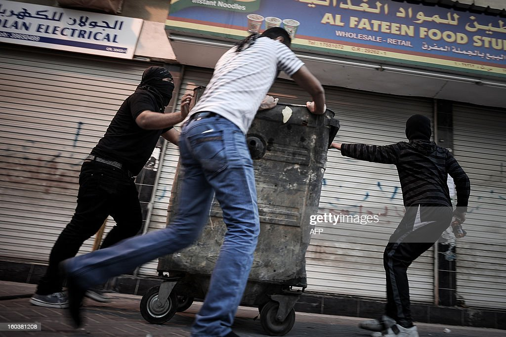 Bahraini Shiite Muslims push a garbage container to block a road during clashes with riot police following an anti-government demonstration against the death of a child, in the village of Daih, west of Manama, on January 30, 2013. The child, Qassim Habib Marzooq, died in hospital after developing respiratory complications and his relatives claim that his death is due to the inhalation of poisonous tear gas that riot police used during a protest in January 2013.