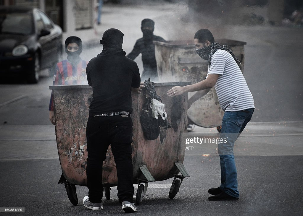 Bahraini Shiite Muslims push garbage containers to block a road during clashes with riot police following an anti-government demonstration against the death of a child, in the village of Daih, west of Manama, on January 30, 2013. The child, Qassim Habib Marzooq, died in hospital after developing respiratory complications and his relatives claim that his death is due to the inhalation of poisonous tear gas that riot police used during a protest in January 2013.