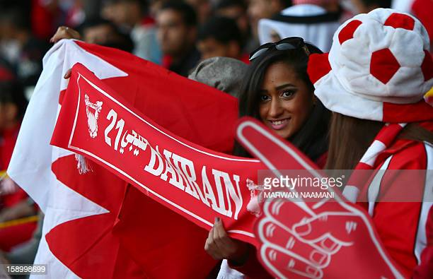 A Bahraini supporter holds a scarf prior the sart of the opening ceremony and football match between Bahrain and Oman in the 21st Gulf Cup tournament...
