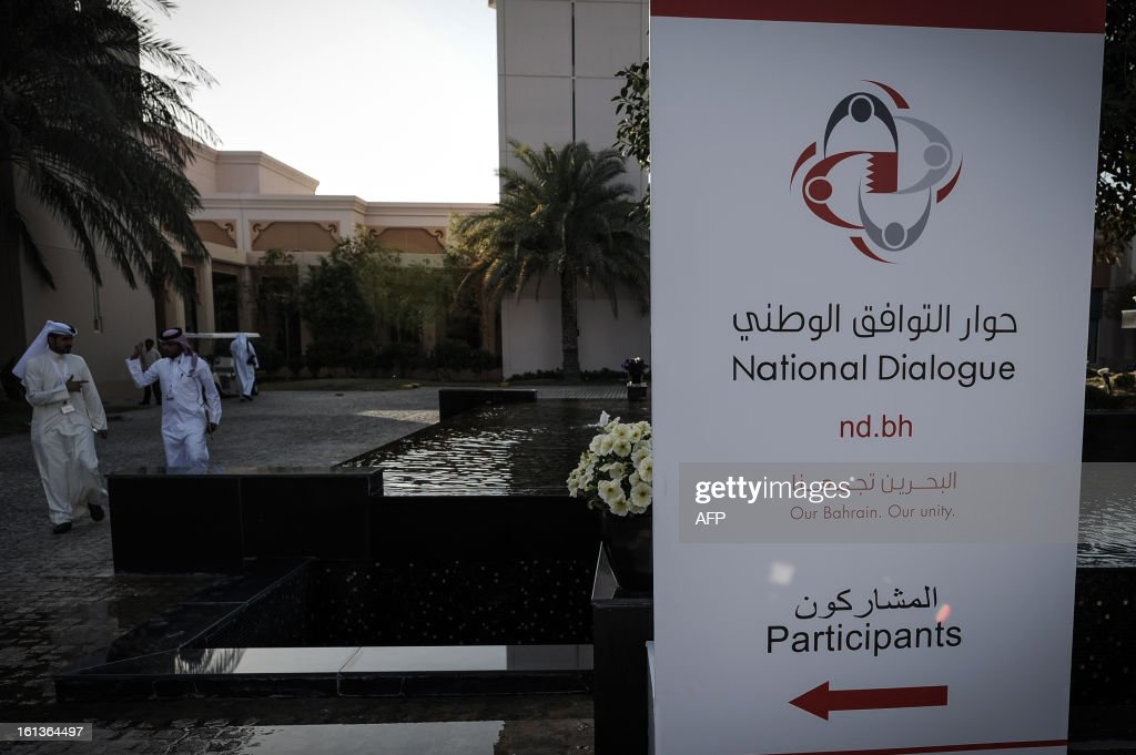 Bahraini walk next to a banner of the National Dialogue in al-Areen Palace Hotel in Zallaq, South of Manama, on February 10, 2013. Bahrain's key political players began a new round of talks on Sunday to try to resolve the kingdom's two-year crisis, after opposition groups made a last-minute decision to join a national dialogue.