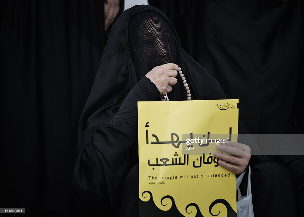 A Bahraini woman holds a placard during an anti-government rally to demand reforms on February 12, 2013 in the village of Sanabis, west of the Bahraini capital Manama. Bahrain's opposition groups, expecting little from a renewed national dialogue, plan to stage protests this week to mark the second anniversary of a Shiite-led uprising that was crushed by security forces.AFP PHOTO/MOHAMMED AL-SHAIKH