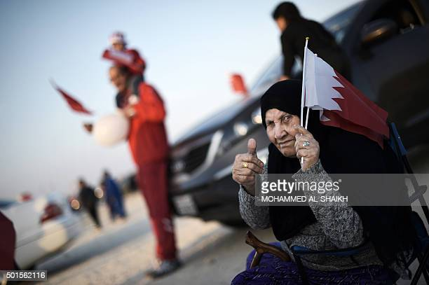 A Bahraini woman holds national flags as people celebrate Bahrain National Day in Sakhir south of Manama on December 16 2015 AFP PHOTO / MOHAMMED...