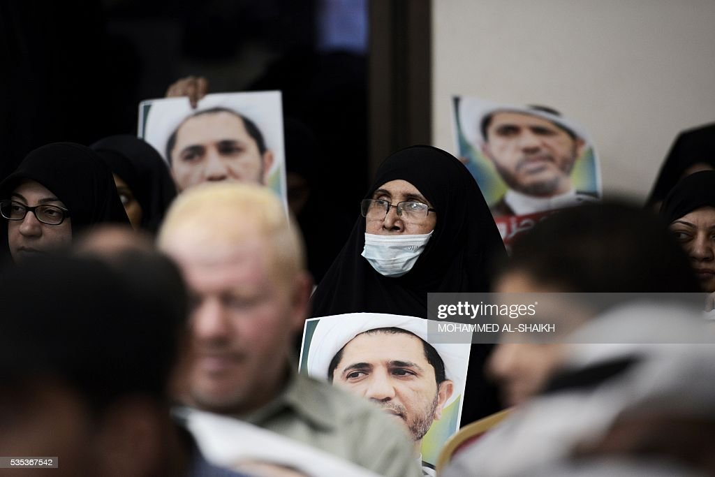 A Bahraini woman holds placards bearing the portrait of Sheikh Ali Salman, head of the Shiite opposition movement Al-Wefaq, during a protest on May 29, 2016 against his arrest, at Al wefaq headquarter building, in the village of Zinj on the outskirts of the capital Manama. / AFP / MOHAMMED
