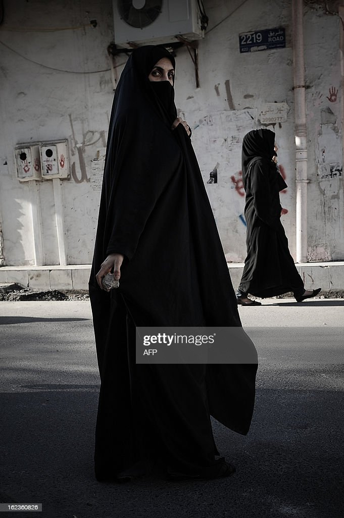 A Bahraini woman holds stones during clashes with riot police following an anti-regime protest against the killing of 20-year old Mahmud al-Jaziri, in the village of Daih, West of Manama, on February 22, 2013. The Shiite protester died of wounds after he was shot during clashes with Bahraini police on the second anniversary of the February 14, 2011 uprising. AFP PHOTO/MOHAMMED AL-SHAIKH