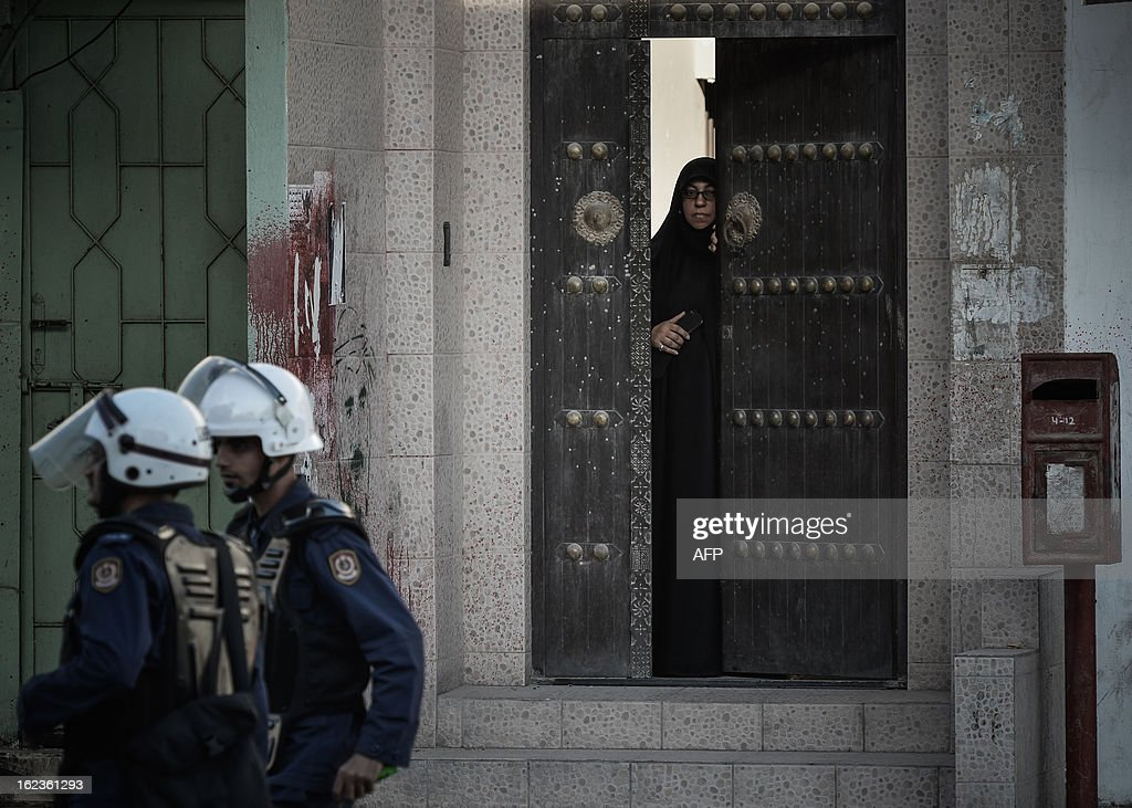 A Bahraini woman looks out of her doorway at riot police during clashes following an anti-regime protest against the killing of 20-year old Mahmud al-Jaziri, in the village of Daih, West of Manama, on February 22, 2013. The Shiite protester died of wounds after he was shot during clashes with Bahraini police on the second anniversary of the February 14, 2011 uprising.