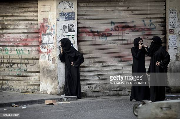 A Bahraini woman peers down a street during clashes with riot police following the funeral of Mohammed Abdul Jalil in the village of Daih west of...