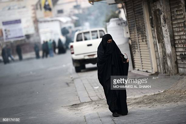 A Bahraini woman runs for cover from tear gas fired by riot police during clashes in the village of Jidhafs west of Manama following a protest...