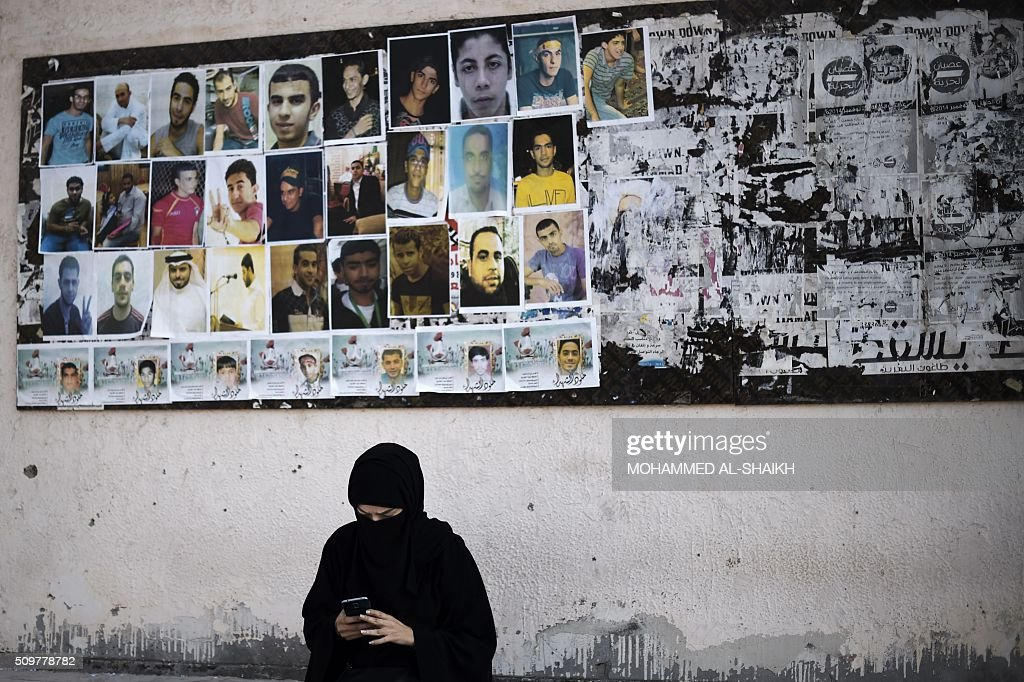 A Bahraini woman sits near portraits of jailed political activists and protesters killed during clashes with police, before taking part in a demonstration to mark the fifth anniversary of the Arab Spring-inspired uprising in the mainly Shiite village of Sitra, south of Manama, on February 12, 2015. Five years after Sunni-ruled Bahrain crushed a popular uprising by the Shiite majority, the kingdom is locked in a political impasse exacerbated by an economic crisis, analysts say. / AFP / MOHAMMED AL-SHAIKH