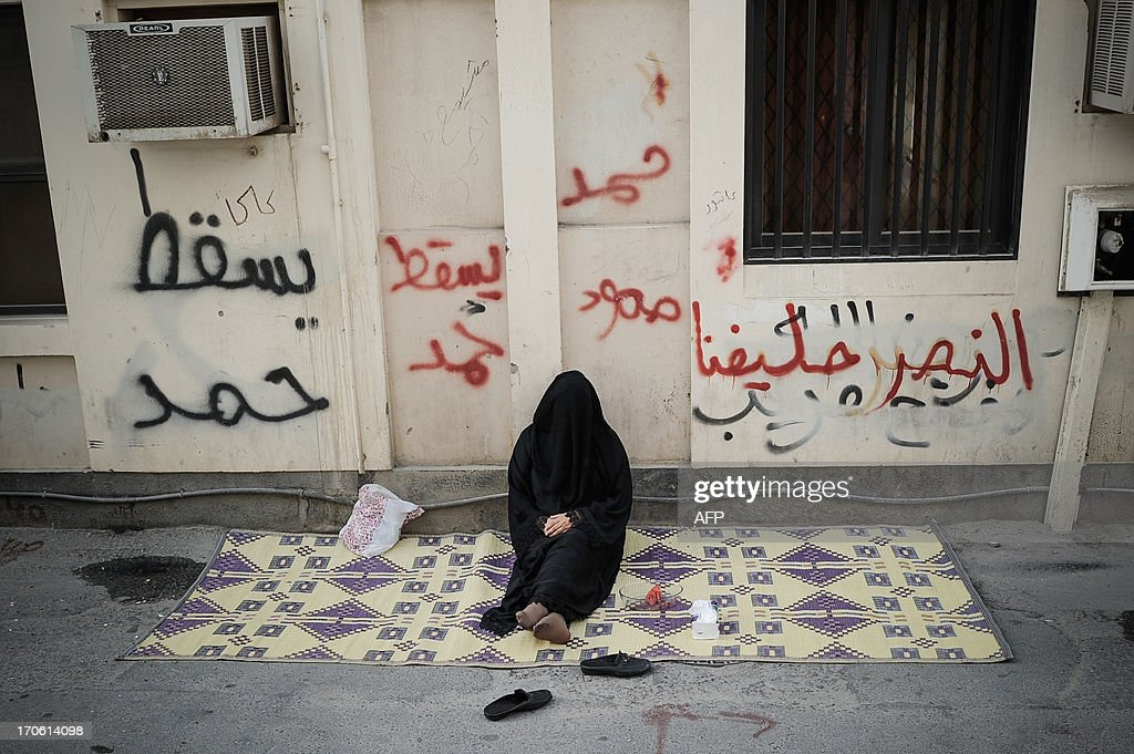 A Bahraini woman sits outside a home waiting for a protest to start in the village of Bilad al-Qadeem, in a suburb of Manama, on June 15, 2013. Weekly protests, that began in 2011, are held by Bahraini Shiite Muslims demanding more rights from the ruling Sunni Muslim dynasty.