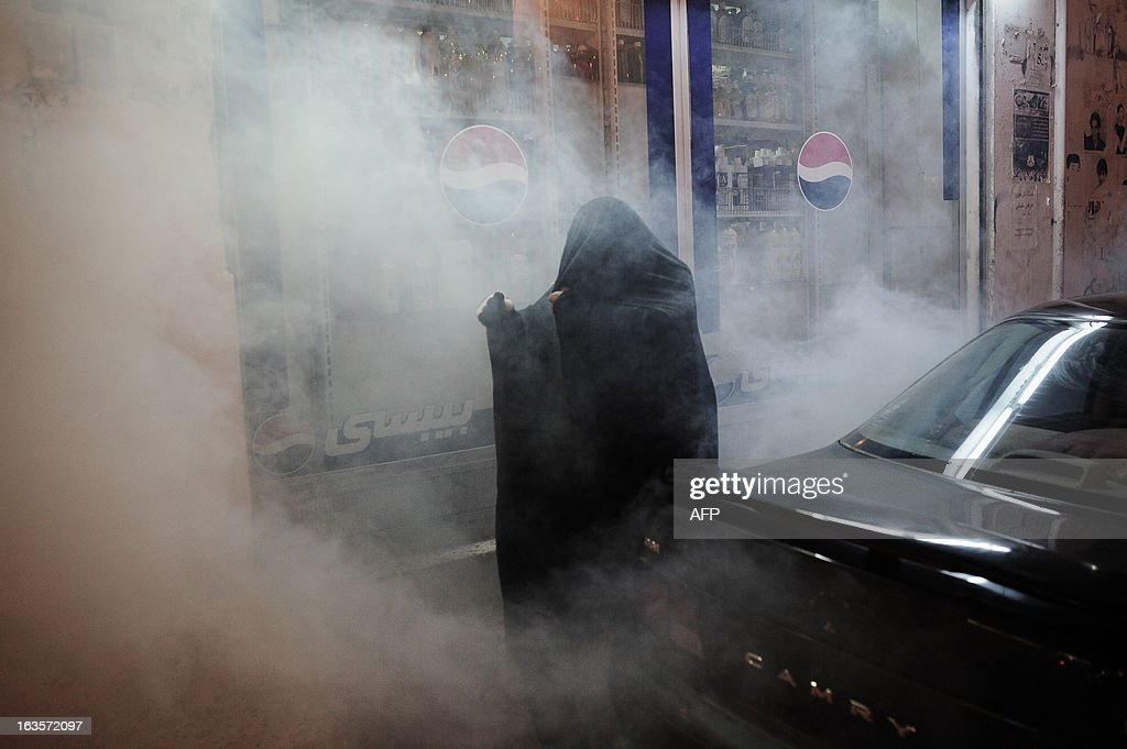 A Bahraini woman tries to run for cover from tear gas fired by riot police during an anti-government protest in the village of Sanabis, West of Manama, on March 12, 2013. Bahrain's opposition groups, plan to stage protests this week to mark the second anniversary of the entry of Saudi troops to Bahrain during an uprising in the Sunni-ruled kingdom on March 2011.