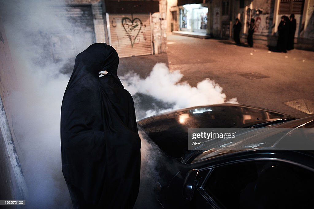 A Bahraini woman tries to run for cover from tear gas fired by riot police during an anti-government protest in the village of Sanabis, West of Manama, on March 12, 2013. Bahrain's opposition groups, plan to stage protests this week to mark the second anniversary of the entry of Saudi troops to Bahrain during an uprising in the Sunni-ruled kingdom on March 2011. AFP PHOTO/MOHAMMED AL-SHAIKH
