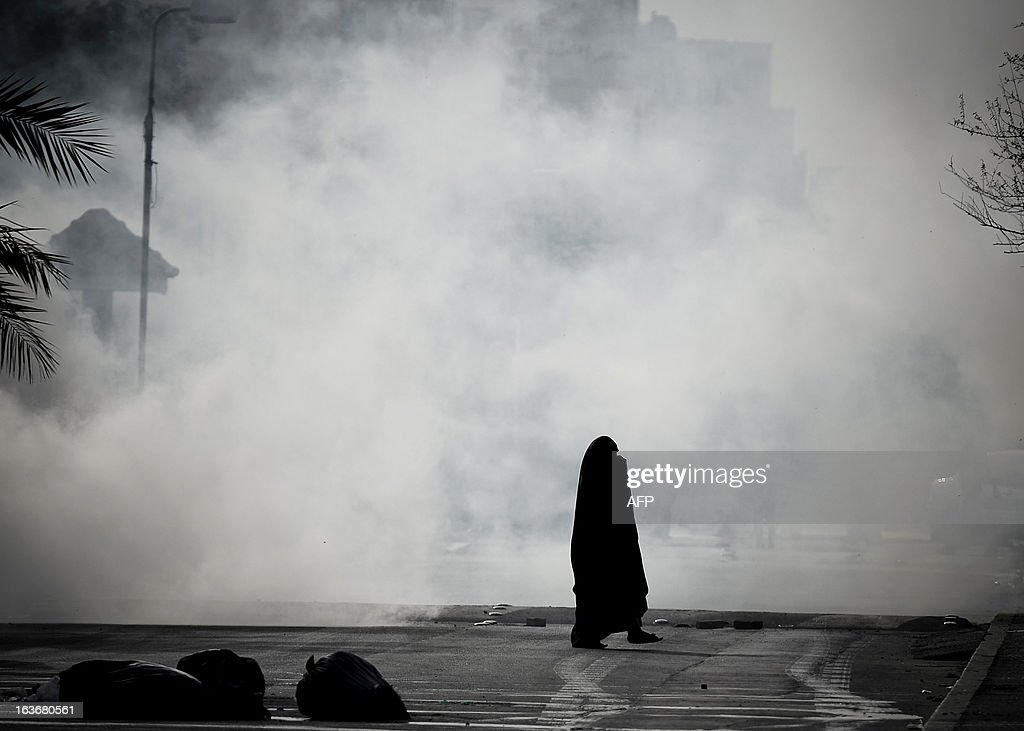 A Bahraini woman tries to run for cover from tear gas fired by riot police during an anti-government demonstration in the village of Sanabis, West of Manama, on March 14, 2013. Bahraini police clashed with youths protesting against the deployment into a third year of a Gulf military force that backed Manama's bid to crush a Shiite-led uprising, witnesses said.