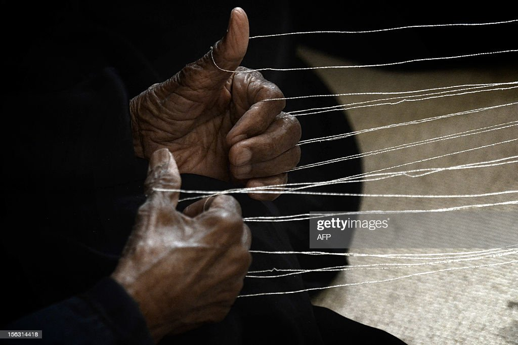 A Bahraini woman uses her fingers to hold loops of yarn during a weaving demostration at the Sheikh Ibrahim Al-Khalifa Cultural Center in Muharraq City, east of the capital Manama on November 12, 2012.
