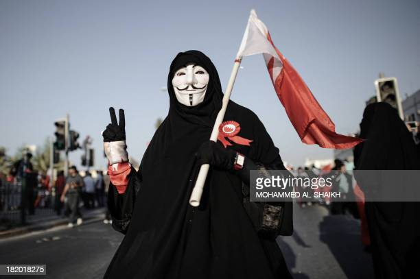 A Bahraini woman wearing a Guy Fawkes mask used by the Anonymous movement flashes the 'Vsign' for victory during an antigovernment protest in the...