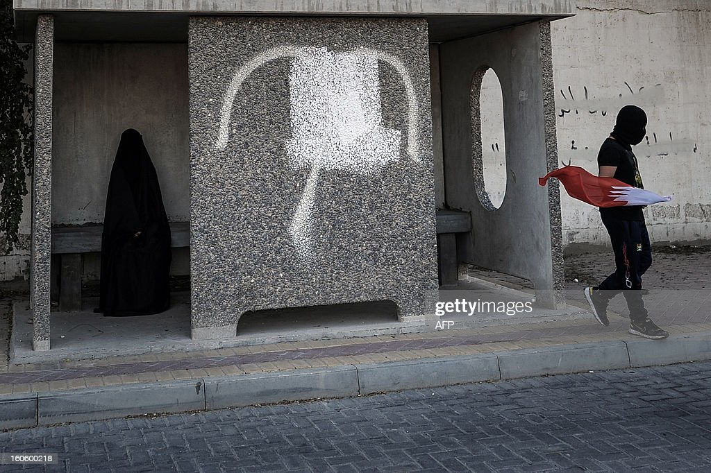 A Bahraini woman, wearing the niqab, sits at a bus stop as a Bahraini Shiite Muslim demonstrator walks by holding his national flag during an anti-government rally to demand reforms in the village of Malikiya, South of Manama, on February 3, 2013. The Gulf state has been shaken by unrest since its forces in March 2011 crushed a month of popular Shiite-led protests demanding greater rights and an end to what they said was discrimination by the Sunni royals. AFP PHOTO/MOHAMMED AL-SHAIKH