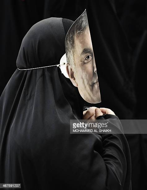 A Bahraini woman wears a mask featuring a portrait of jailed prominent Shiite human rights activist Nabeel Rajab during an antigovernment protest in...
