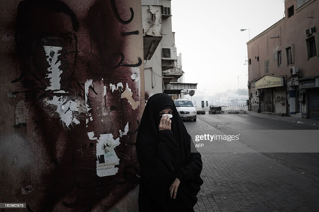 A Bahraini woman wipes her face after riot police fired tear gas to disperse protesters who tried to reach Salmaniya hospital to retrieve the body of Mahmud al-Jaziri in the village of Zinj, a suburb of Manama, on March 2, 2013. Jaziri, 20, succumbed to his wounds on February 21 after he was shot during clashes between police and protesters marking the second anniversary of the February 14, 2011 uprising. His family says Bahraini authorities have not handed over his body because of a dispute over the location of the planned funeral. AFP PHOTO/MOHAMMED AL-SHAIKH