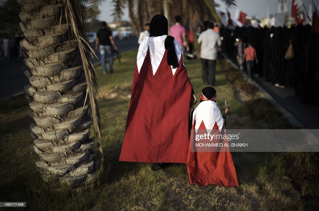A Bahraini woman with her daughter, with the national flag draped across their shoulders, take part in an anti-government protest in the village of Diraz, west of Manama, on June 6, 2014. AFP PHOTO/MOHAMMED AL-SHAIKH