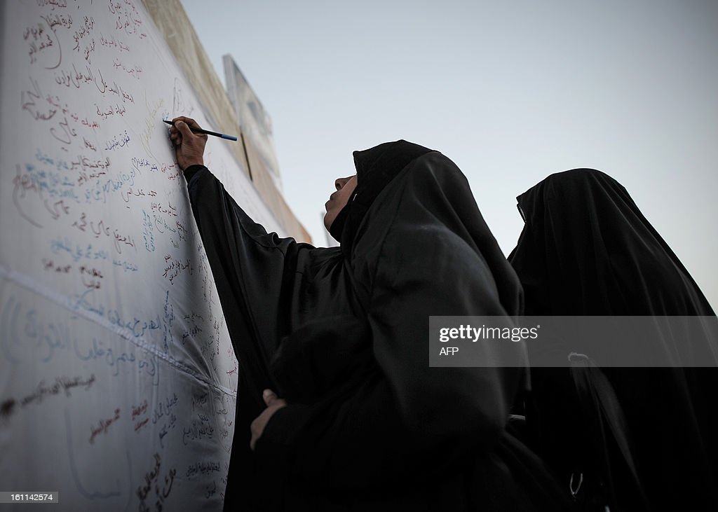 A Bahraini woman writes on a white sheet the names of her a relative detained during an anti-government rally to demand reforms on February 9, 2013 in the village of Al Muqsha, west of the Bahraini capital Manama. Bahrain's national dialogue is set to resume on February 10, in an atmosphere of mutual mistrust between government and the opposition ahead of the second anniversary of a Shiite-led uprising that shook the Gulf kingdom. AFP PHOTO/MOHAMMED AL-SHAIKH