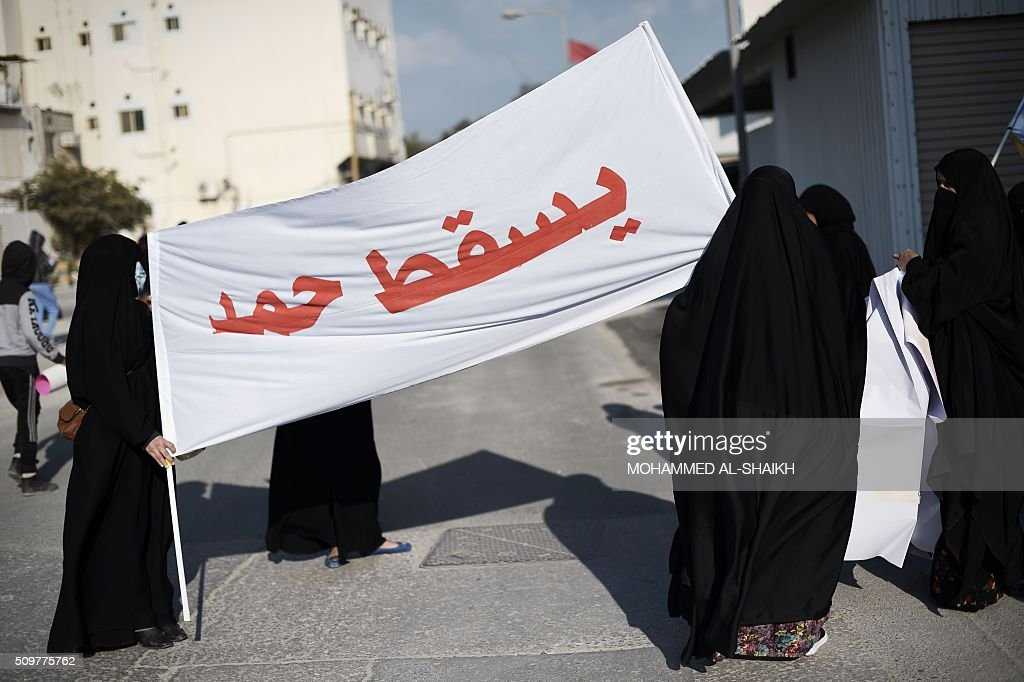 Bahraini women hold a banner reading in Arabic 'Down Hamad', referring to Bahrain's king, during a demonstration to mark the fifth anniversary of the Arab Spring-inspired uprising, on February 12, 2015, in the mainly Shiite village of Sitra, south of Manama. Five years after Sunni-ruled Bahrain crushed a popular uprising by the Shiite majority, the kingdom is locked in a political impasse exacerbated by an economic crisis, analysts say. / AFP / MOHAMMED AL-SHAIKH
