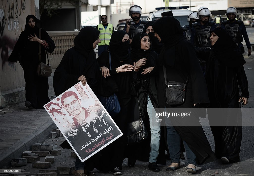 Bahraini women hold a poster of killed protester Mahmud al-Jaziri with a slogan reading in Arabic 'Honouring the dead is to bury him, where is humanity?' as they try to reach Salmaniya hospital to retrieve Jaziri's body in the village of Zinj, a suburb of Manama, on March 2, 2013. Jaziri, 20, succumbed to his wounds on February 21 after he was shot during clashes between police and protesters marking the second anniversary of the February 14, 2011 uprising. His family says Bahraini authorities have not handed over his body because of a dispute over the location of the planned funeral. AFP PHOTO/MOHAMMED AL-SHAIKH